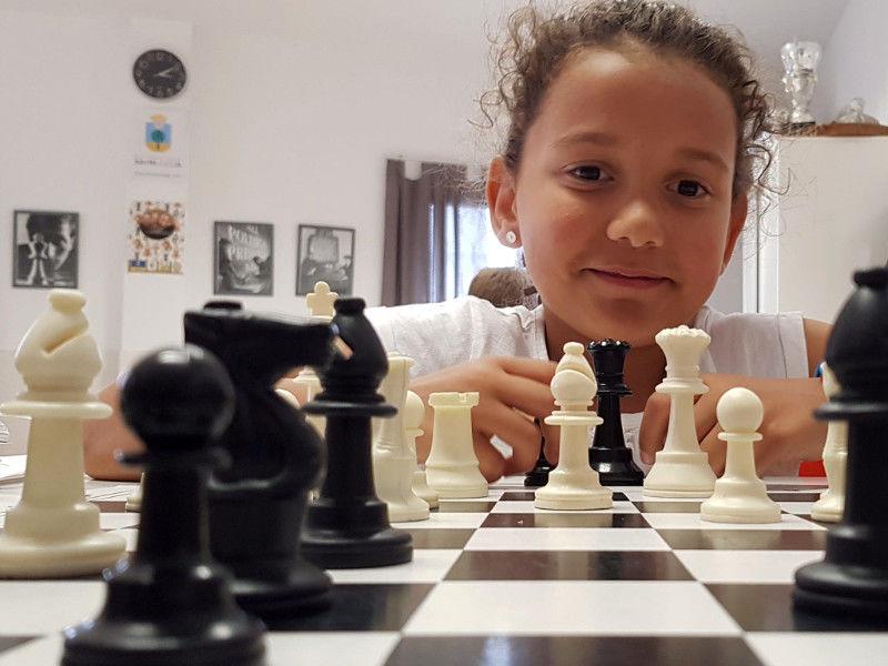 Niña jugando al ajedrez en La Escuelita